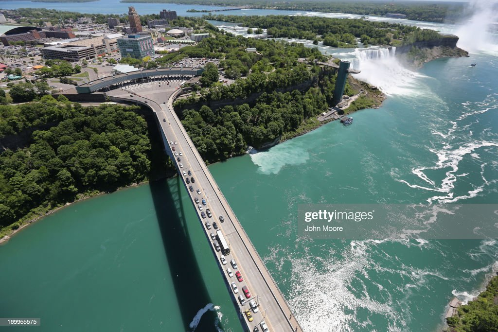 The Rainbow Bridge crosses from the United States (L), into Canada near the Niagara Falls on June 4, 2013 at Niagara Falls, New York. The falls, which have a combined highest flow rate of any waterfall in the world, straddle the U.S.-Canada border, on the Niagara River, which drains Lake Erie into Lake Ontario. The falls, visited by millions of tourists on each side of the border, are also a major source of hydroelectric power for the region. The aerial view was seen from a helicopter flown by the U.S. Office of Air and Marine, (OAM), which monitors and patrols the U.S. northern border with Canada.