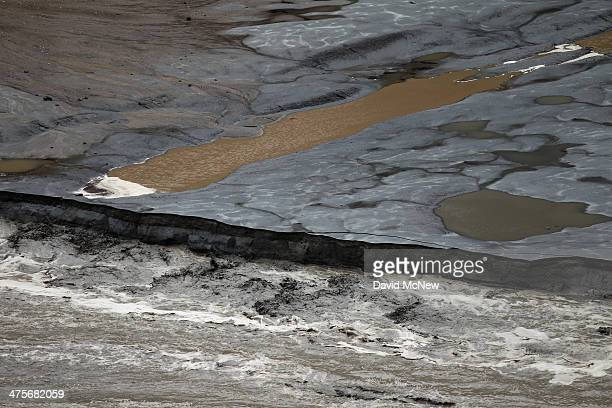 The rainmuddied San Gabriel River bites into exposed lake bottom as it rushes into upper reaches of the low waters of San Gabriel Reservoir in the...