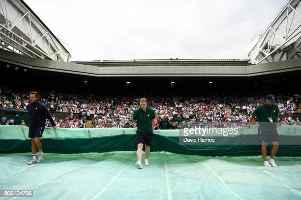 The rains covers are pulled across centre court during the Gentlemen's Singles first round match between Andy Murray of Great Britain and Alexander...