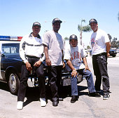 The rap group NWA leans upon the hood of a California police car from left to right they are Dr Dre MC Ren EazyE and DJ Yella 1990