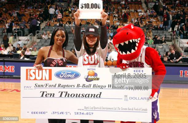 The Raptor and LaToya of the Raptors Dance Pak present a $10000 check to the lucky winner of the Toronto Sun/Ford Raptors BBall Bingo contest during...