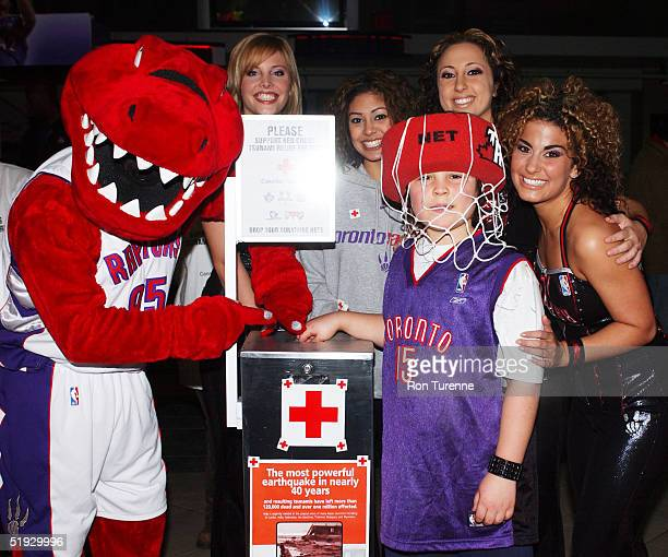 The Raptor and members of the Raptors Dance Pak join 8 yearold Raptor fan Nicholas in helping raise funds for the Red Cross Tsunami Relief fund...