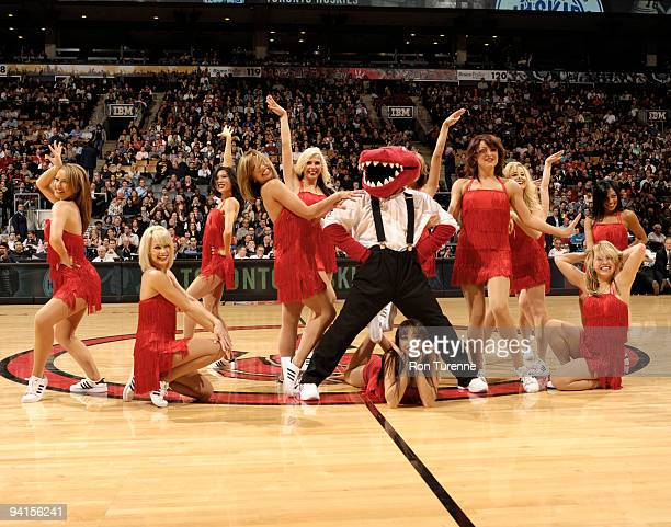 The Raptor poses with the Raptors Dance Pack after a routine to honour the Toronto Huskies during a game featuring the Toronto Raptors and the...
