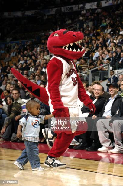 The Raptor the Toronto Raptors mascot entertains the crowd with a young guest during a game between the Boston Celtics and the Toronto Raptors on...