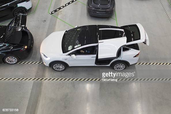 The rear gull wing door of a Tesla Model X sports utility vehicle sits open following assembly for the European market at the Tesla Motors Inc...