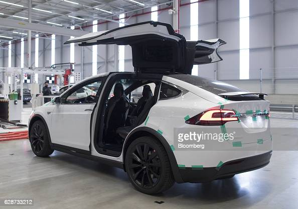 The rear gull wing doors of a Tesla Model X sports utility vehicle sit open following assembly for the European market at the Tesla Motors Inc...