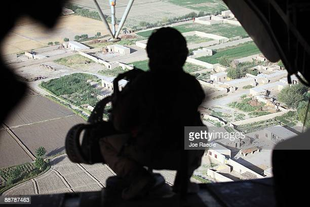 The rear gunner on a US Marine helicopter keeps an eye out as they fly US Marines from 2nd Marine Expeditionary Brigade RCT 2nd Battalion 8th Marines...