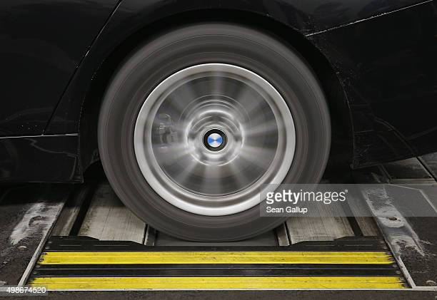 The rear wheels of a car spin as the car undergoes standard emissions testing under laboratory conditions during a workshop for media on automobile...