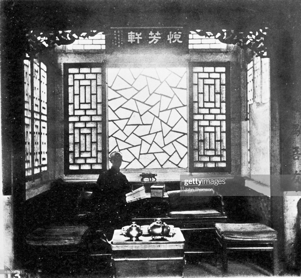 The reception hall at the home of Mr Yang a wealthy official in Beijing China circa 1871 The window is glazed with European glass Above it is an...