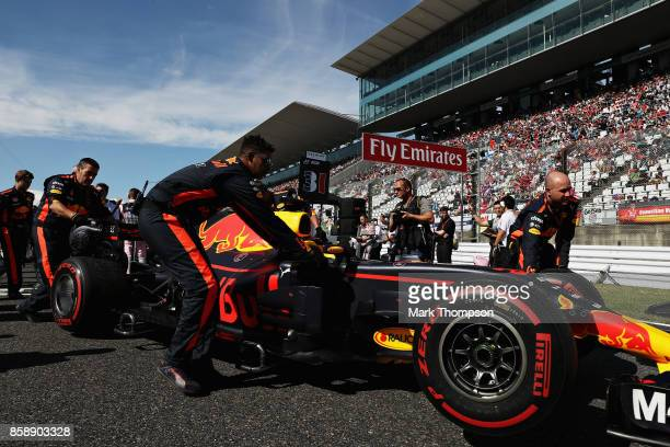 The Red Bull Racing team prepare the car of Daniel Ricciardo of Australia and Red Bull Racing on the grid before the Formula One Grand Prix of Japan...