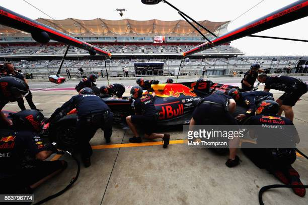 The Red Bull Racing team work on the car of Daniel Ricciardo of Australia and Red Bull Racing in the Pitlane during practice for the United States...