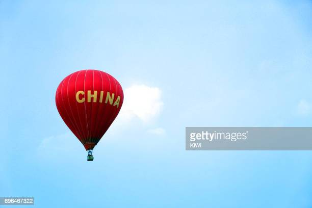 The red hot air balloon is flying on the blue sky