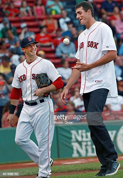 The Red Sox Daniel Nava left looks up at John Isner the top ranked American tennis player in the world after he caught his ceremonial first pitch...