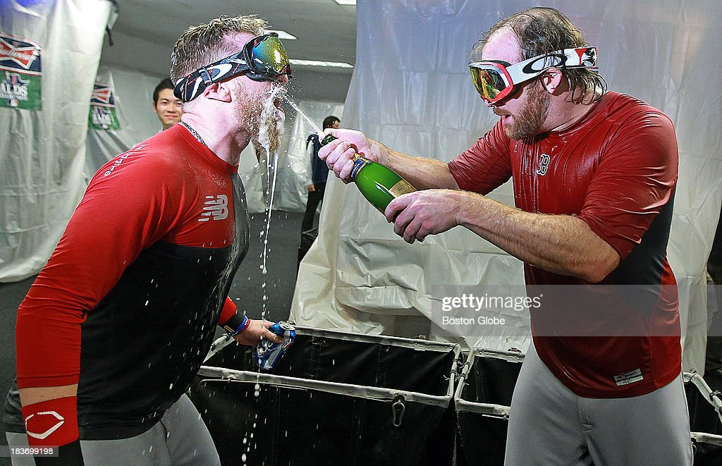 The Red Sox Mike Carp, left, is doused with champagne by teammate Ryan Dempster, right, as they celebrate in the clubhouse. The Boston Red Sox visited the Tampa Bay Rays in Game Four of the ALDS baseball playoffs at Tropicana Field.