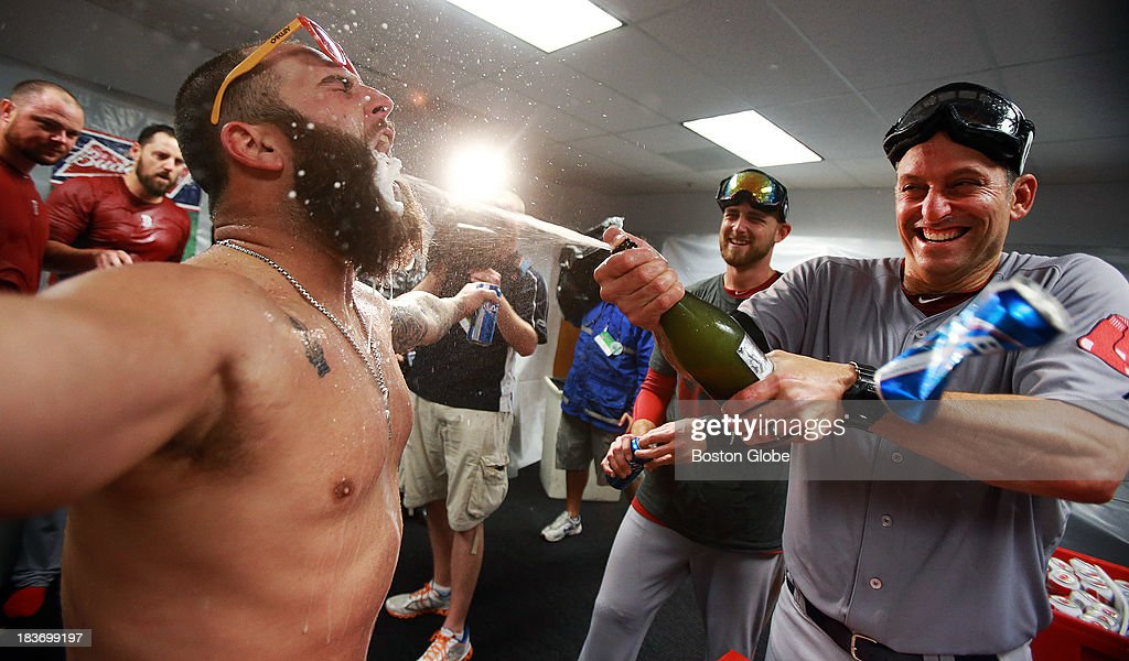 The Red Sox Mike Napoli, left, opens wide for a champagne bath from bench coach Torey Lovullo, right, as they celebrate in the clubhouse. The Boston Red Sox visited the Tampa Bay Rays in Game Four of the ALDS baseball playoffs at Tropicana Field.