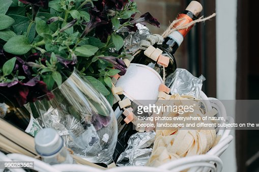 The red wine unopened bottle, glass and blossom flowers in the white basket : Stock Photo