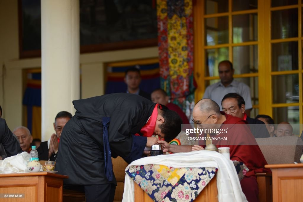 The re-elected Sikyong (Prime Minister of the Central Tibetan Administration) Lobsang Sangay (L) is blessed by Tibetan Spiritual leader the Dalai Lama during Sangay's swearing-in ceremony at the Tsuglakhang Temple in McLeod Ganj on May 27, 2016. The Dalai Lama warned May 27 of a growing divide among exiled Tibetans, saying that morals are 'degenerating' in the community, as the leader of its government-in-exile was sworn in at a ceremony in India. / AFP / Lobsang Wangyal
