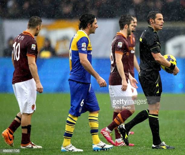 The referee Andrea De Marco leaves the field with players after the match is suspended due to heavy rain during the Serie A match between AS Roma and...