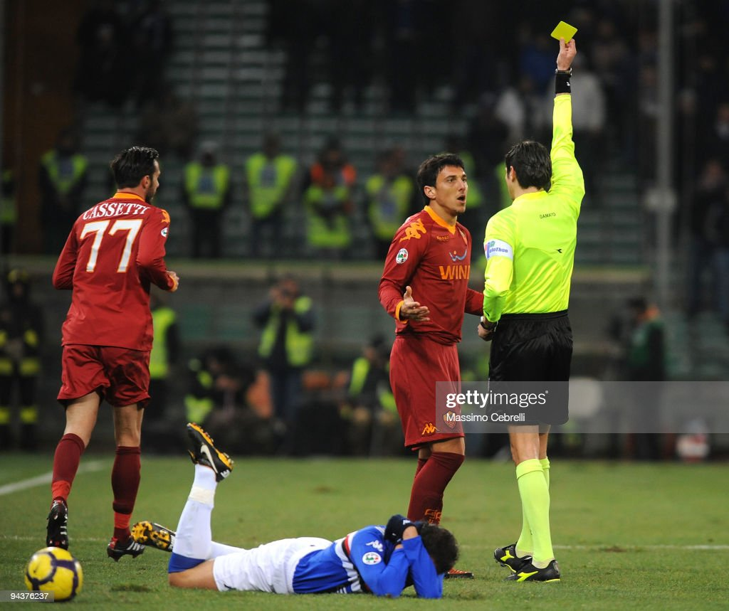 The referee Antonio Damato shows a yellow card toward <a gi-track='captionPersonalityLinkClicked' href=/galleries/search?phrase=Nicolas+Burdisso&family=editorial&specificpeople=490963 ng-click='$event.stopPropagation()'>Nicolas Burdisso</a> of AS Roma during the Serie A match between UC Sampdoria and AS Roma at Stadio Luigi Ferraris on December 13, 2009 in Genoa, Italy.