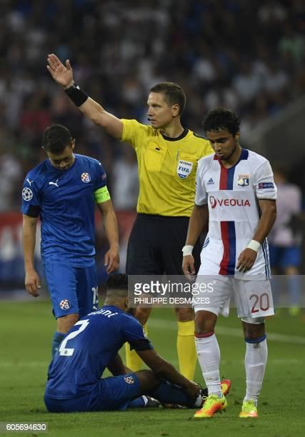 The referee gestures next to Dinamo Zagreb's Algerian forward El Arabi Hilal Soudani and Lyon's Brazilian defender Rafael Da Silva during the...