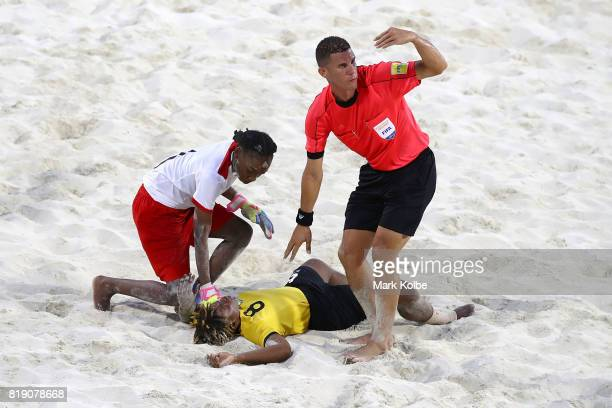 The referee gestures to the sideline as Alexis Woodside of the Bahamas lies injured on the ground during the Girls Beach Soccer match 3 between the...