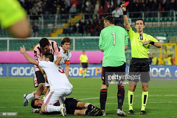 The referee Gianluca Aureliano shows a a red card to Antonio Donnarumma goalkeeper of Milan as Marco Giovio of Palermo lies injured during the...