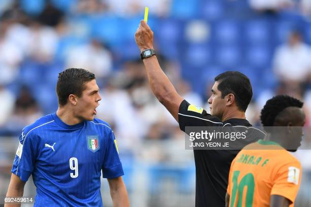 The referee gives a yellow card to Italy's forward Andrea Favilli during the U20 World Cup quarterfinal football match between Italy and Zambia in...