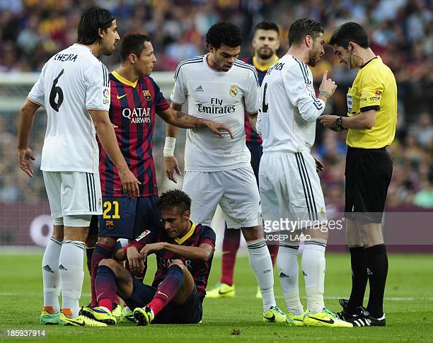 The referee hands Real Madrid's defender Sergio Ramos a yellow card as Barcelona's Brazilian forward Neymar da Silva Santos Junior sits on the ground...
