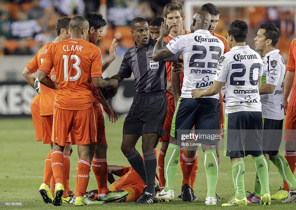 The referee has to separate the teams after hard tackle on Boniek Garcia #27 of Houston Dynamo during the second half at BBVA Compass Stadium on March 5, 2013 in Houston, Texas.
