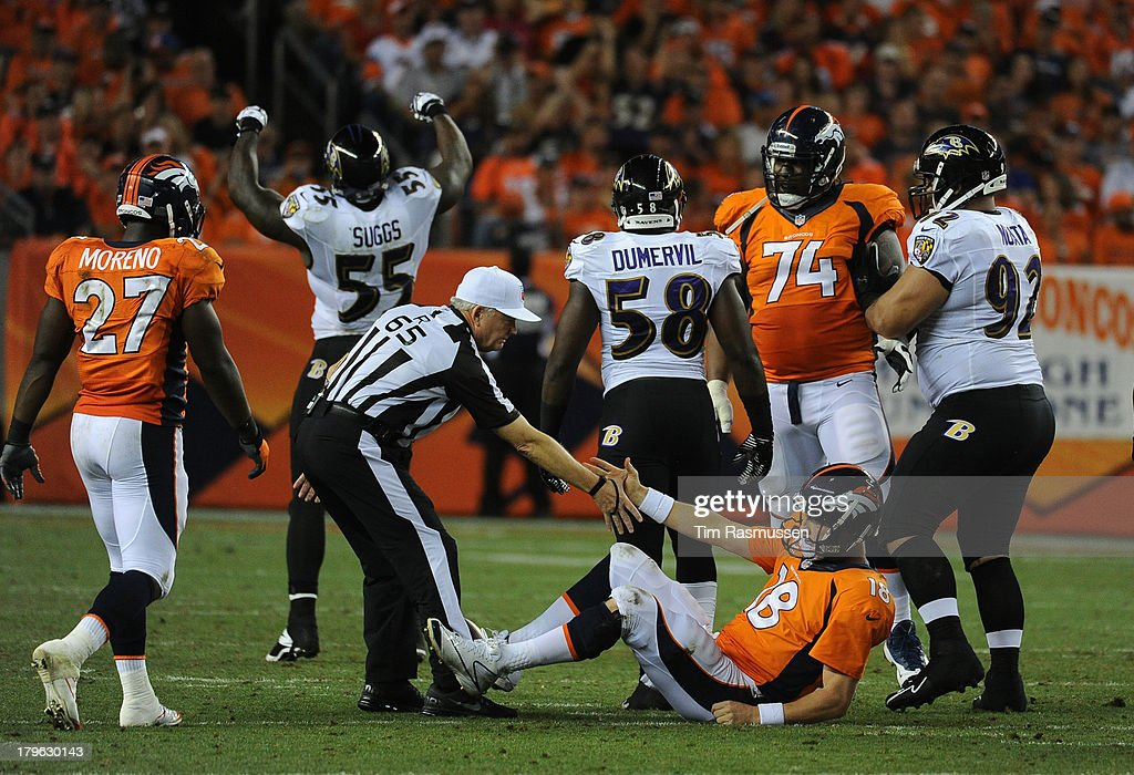 The referee helps Denver Broncos quarterback Peyton Manning (18) up in the third quarter. The Denver Broncos took on the Baltimore Ravens in the first game of the 2013 season at Sports Authority Field at Mile High in Denver on September 5, 2013.