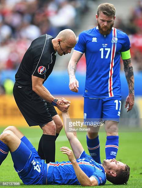 The referee helps up Kari Arnason of Iceland during the UEFA EURO 2016 Group F match between Iceland and Austria at Stade de France on June 22 2016...