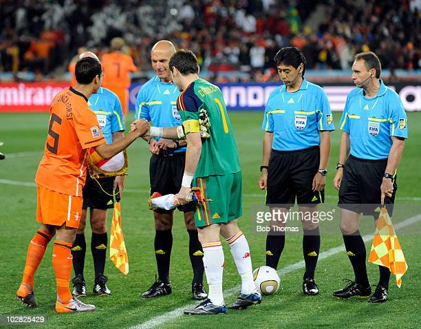 The referee Howard Webb looks on as the Netherlands captain Giovanni Van Bronckhorst shakes hands with Spanish captain Iker Casillas before the start...