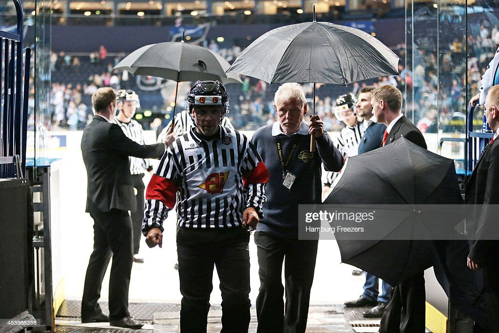The Referee is protected with umbrella during the Champions Hockey League group stage game between Hamburg Freezers and Lulea Hockey on August 22, 2014 in Hamburg, Germany.