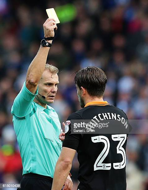 The referee issues Sam Hutchinson of Sheffield Wednesday a yellow card during the Sky Bet Championship match between Huddersfield Town and Sheffield...