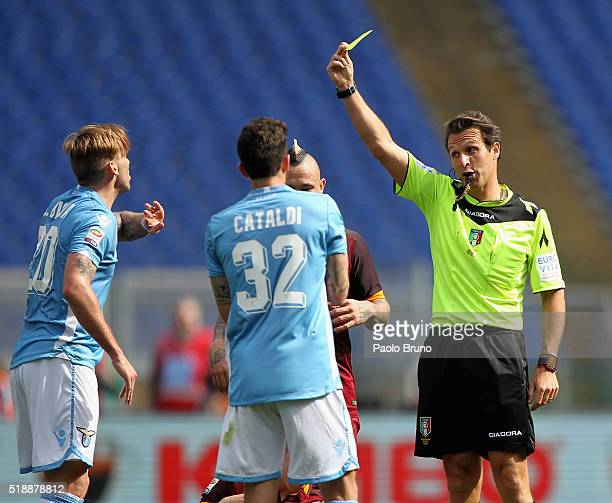 The referee Luca Banti shows the yellow card to Lucas Biglia of SS Lazio during the Serie A match between SS Lazio and AS Roma at Stadio Olimpico on...