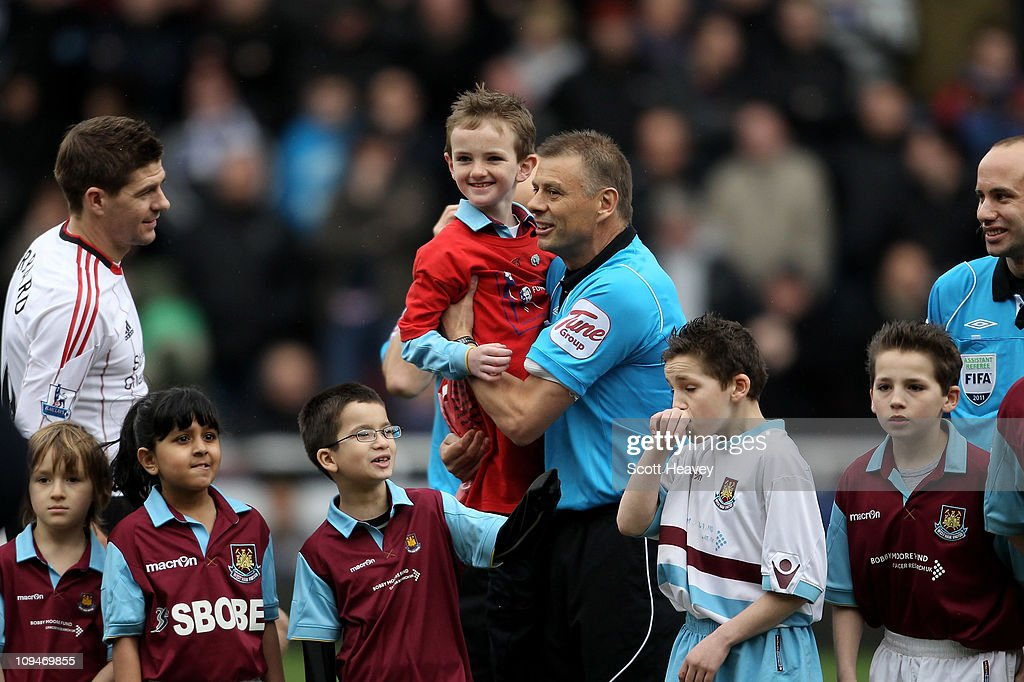 The referee <a gi-track='captionPersonalityLinkClicked' href=/galleries/search?phrase=Mark+Halsey&family=editorial&specificpeople=224397 ng-click='$event.stopPropagation()'>Mark Halsey</a> (4R) holds up Jonjo Heuerman as he completes his charity walk from Wembely to Upton Park in aid of the Bobby Moore Fund for cancer research ahead of the Barclays Premier League match between West Ham United and Liverpool at the Boleyn Ground on February 27, 2011 in London, England.