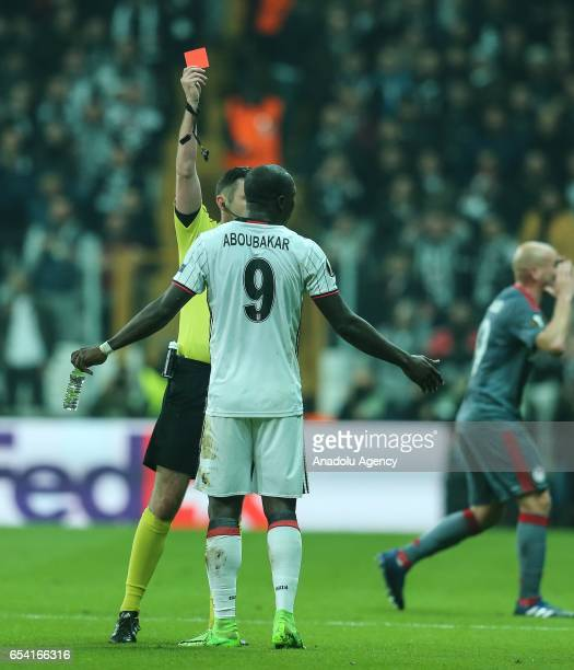 The referee Michael Oliver shows a red card to Vincent Aboubakar of Besiktas during the UEFA Europa League Round 16 secondleg match between Besiktas...
