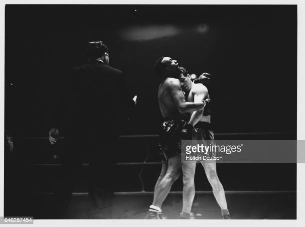 The referee moves in to separate a clinch between Len Harvey and Larry Gains during their fight for the vacant British Empire heavyweight title at...