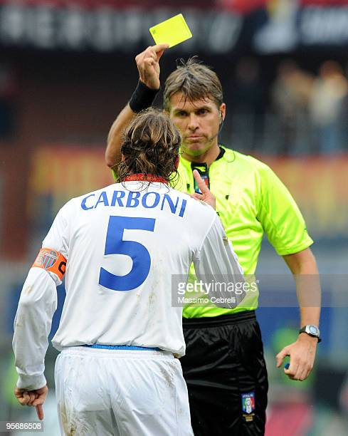 The referee Roberto Rosetti shows a yellow card toward Ezequiel Alejo Carboni of Catania Calcio during the Serie A match between Genoa CFC and...