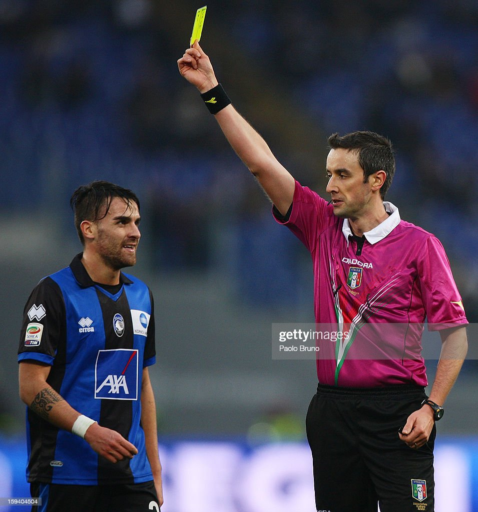 The referee Sebastiano Peruzzo (R) shows the yellow card to <a gi-track='captionPersonalityLinkClicked' href=/galleries/search?phrase=Luca+Cigarini&family=editorial&specificpeople=3933790 ng-click='$event.stopPropagation()'>Luca Cigarini</a> of Atalanta BC during the Serie A match between S.S. Lazio and Atalanta BC at Stadio Olimpico on January 13, 2013 in Rome, Italy.