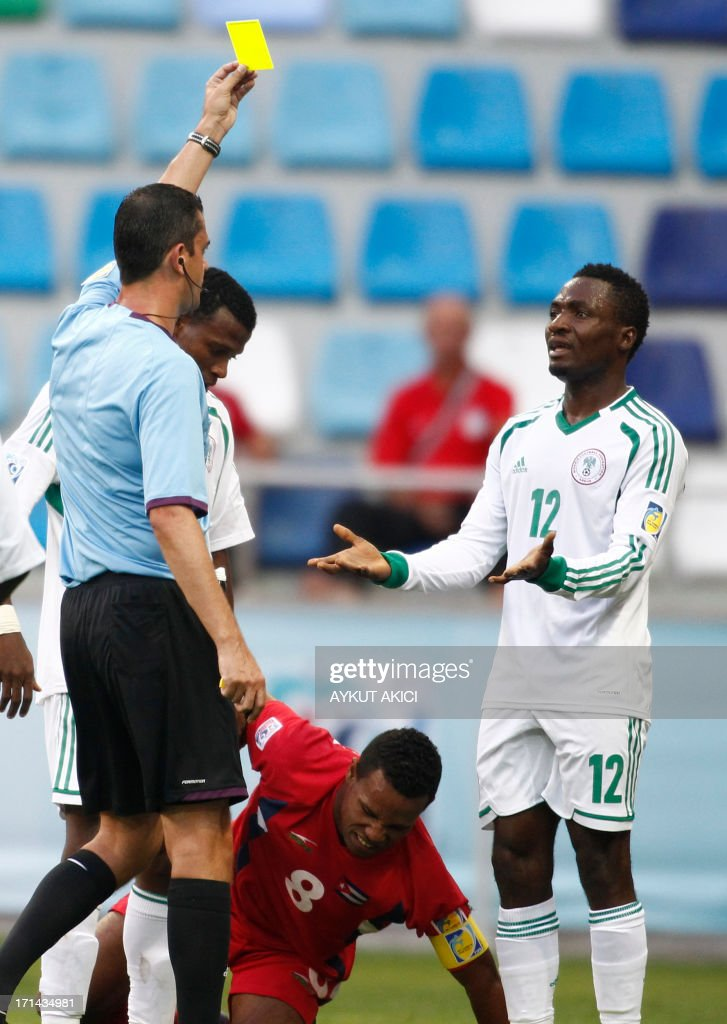 The referee shows a yellow card to Nigeria's Ovbokha Agboyi (R) during the group stage football match between Cuba and Nigeria at the FIFA Under 20 World Cup at the Kadir Has Stadium in Kayseri on June 24, 2013. AFP PHOTO /TURKPIX / Aykut AKICI