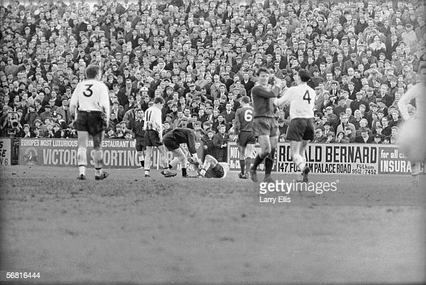 The referee speaks to Fulham striker Mark Pearson who is lying injured after an incident with Liverpool striker Ian St John 26th February 1966 St...