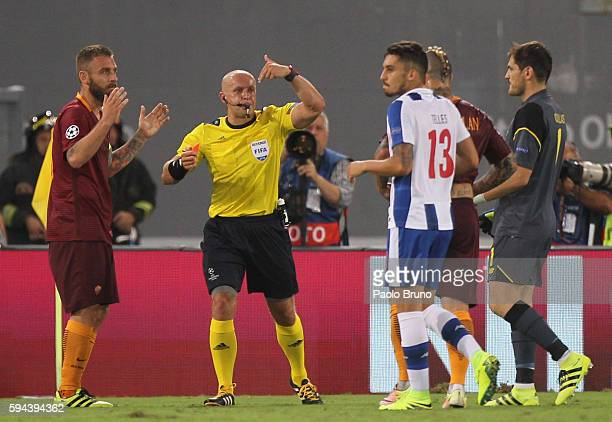 The referee Szymon Marciniak shows the red card to Daniele De Rossi of AS Roma during the UEFA Champions League qualifying playoff round second leg...