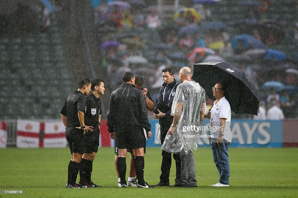 The referees and official inspect the pitch as heavy rain falls prior to the Barclays Asia Trophy Semi Final match between Tottenham Hotspur and Sunderland at Hong Kong Stadium on July 24, 2013 in So Kon Po, Hong Kong.