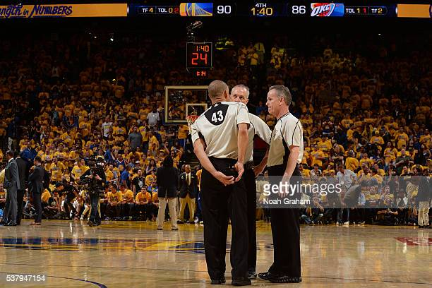 The referees talk with each other during the game between the Golden State Warriors and the Oklahoma City Thunder during Game Seven of the Western...