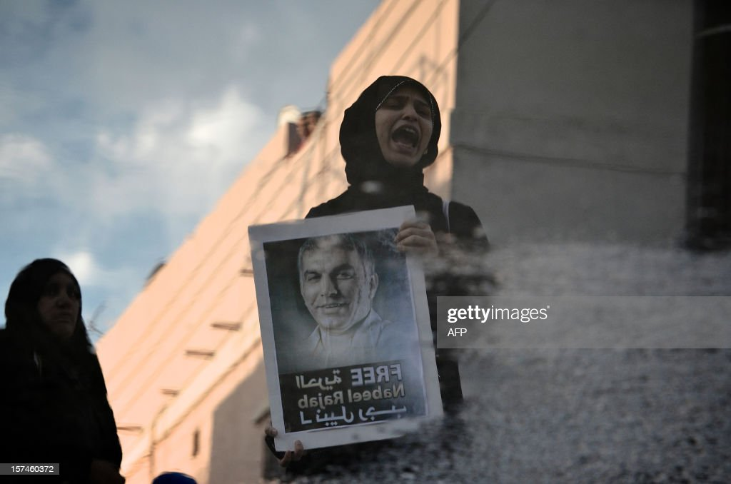 The reflection of a Bahraini Shiite Muslim woman protestor shouting slogans, is seen in a puddle of water during a demonstration in solidarity with political prisoners and against the government in the village of Abu Saiba, West of Manama, on December 3, 2012. Bahrain's Court of Cassation has set a January 7 date to announce its verdict in the trial of 13 Shiite opposition leaders jailed for their role in last year's unrest, their lawyers said.