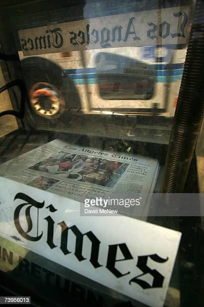 The reflection of a bus passes a rack of Los Angeles Times newspapers for sale April 23 2007 in Los Angeles California The Times announced today that...