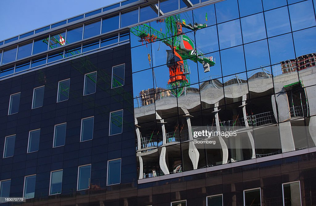 The reflection of a construction crane is seen on the windows of a building in the Mitte district in Berlin, Germany, on Saturday, March 2, 2013. Germany's 10-year government bonds advanced for a second day even before a report that economists said will show producer prices in the euro area increased for the first time in four months in January. Photographer: Krisztian Bocsi/Bloomberg via Getty Images