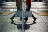 The reflection of a pedestrian carrying a shopping bag is seen in the window of a store in San Francisco California US on Monday July 7 2014 US...