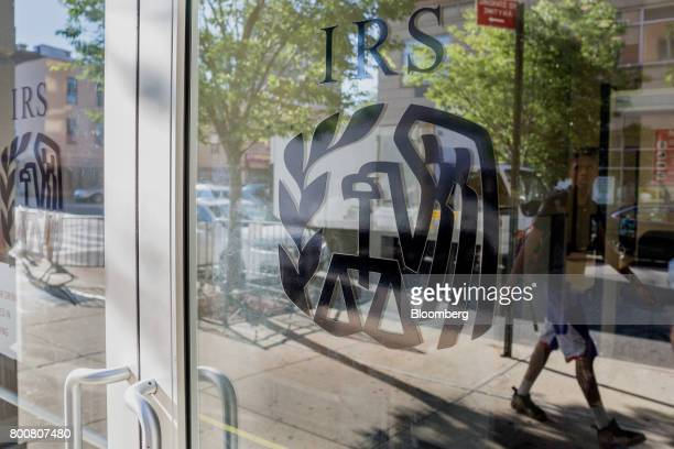 The reflection of a pedestrian is seen walking past an Internal Revenue Service office building in the East Harlem neighborhood of New York US on...